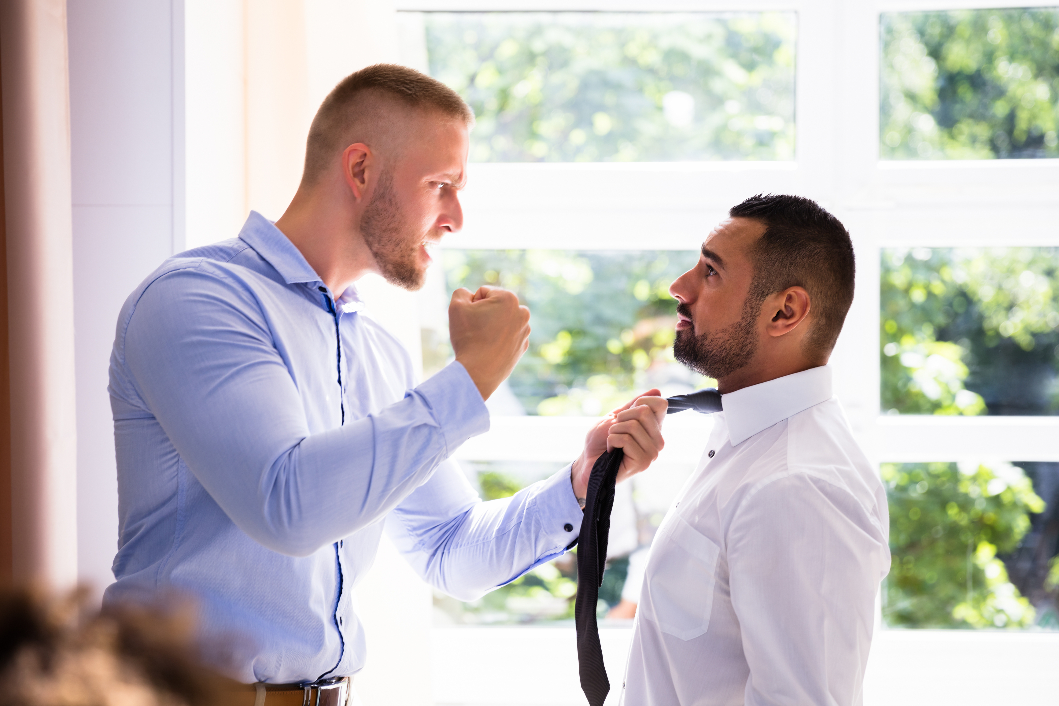 Man threatening another man, displaying workplace violence